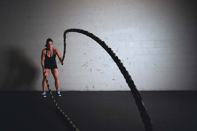 A woman doing a battle ropes exercise