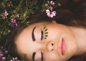 ladys face with eyes closed amidst flowers